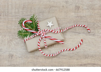 xmas present with fir branch, candy cane and star lying on wood