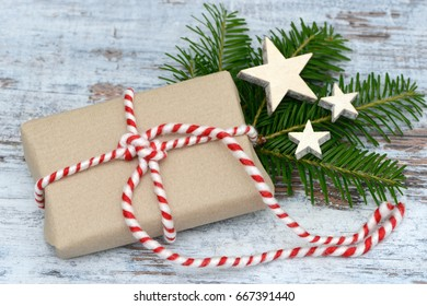 xmas present with fir branch and star lying on wood