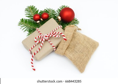 xmas present, santa bag and christmas bauble with fir branch lying on white