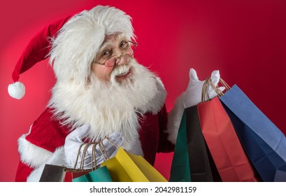 Xmas Santa Claus holding shopping bags on a red background. Emotional senior male model old man with a natural white beard Father Christmas. Joyful character for Black Friday sales and discounts