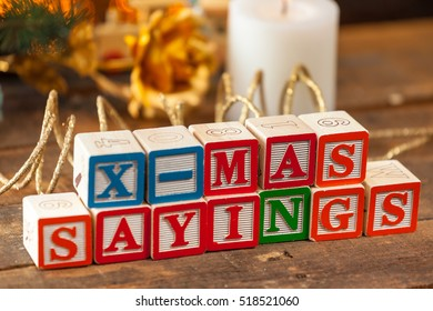 X-Mas Sayings Written With Toy Blocks On Christmas Card Background.