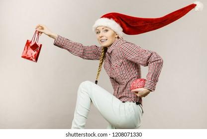 Xmas, seasonal christmas, smart clever shopping concept. Happy woman wearing windblown Santa Claus helper hat, shop bag and fake brain.