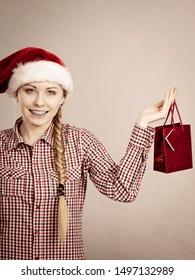 Xmas, seasonal clothing, winter christmas concept. Happy woman wearing windblown Santa Claus helper hat holding shopping bag