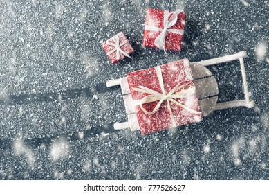 Xmas sledge with red gift boxes on snowy background