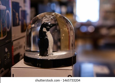 Xmas snowdome in homeware shop. A close-up view of a festive snow globe with a penguin figurine inside, ornamental christmas decoration for sale in small local home wares store.