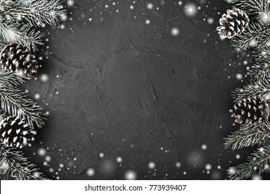 Xmas theme with fir branches, evergreen pines, on snowy black, stone background viewed from above, greeting card with space for text