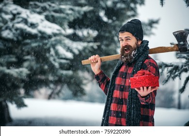 xmas wanderlust, hiking and travel. Christmas hipster lumberjack with ax in wood. New year man in snowy cold forest with gift box. Winter holiday celebration. Man with beard in winter forest with axe.