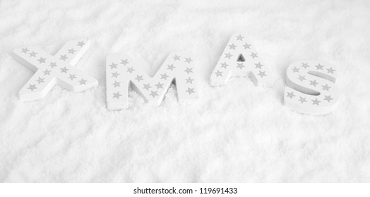 Xmas, white wooden letters with silver stars in snow