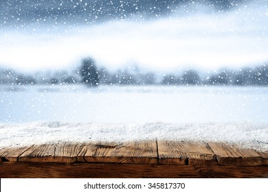 xmas winter blurred background in blue color and shabby wooden table place