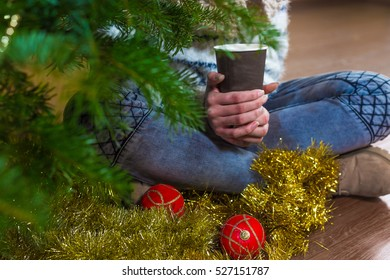 x-mas, winter holidays and people concept - happy young woman standing near a christmas tree with a cup of coffee in her heands