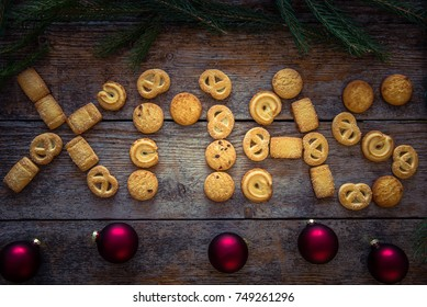 Xmas word made from gingerbread cookies on a wooden background. Christmas background