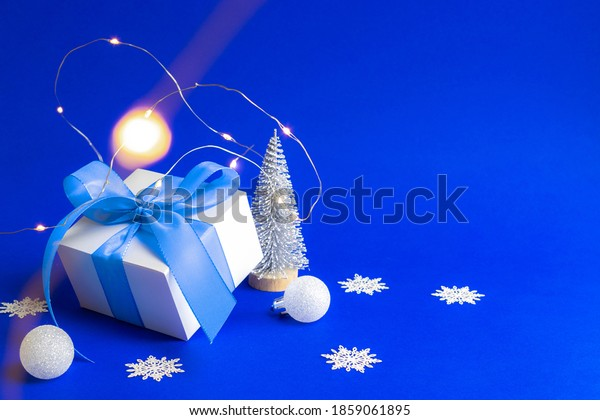 Xmas wreath. White gift box with blue ribbon, winter tree, Snowflakes and Silver balls in Christmas composition on blue background for greeting card. Xmas backdrop with space for text.