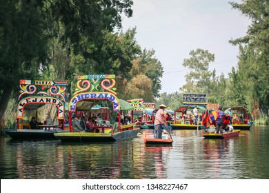 """Xochimilco, Mexico City, Mexico - February 6, 2017: Tourists in different colorful """"trajineras"""" (boats) enjoy a ride on a canal of Xochimilco."""