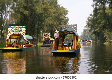"XOCHIMILCO, MEXICO CITY- SEP 3 : Boatmen pole their brightly colored boats September 3, 2008 in Xochimilco, Mexico City. Tourists can rent these boats or ""Trajineras"" complete with food and musicians."