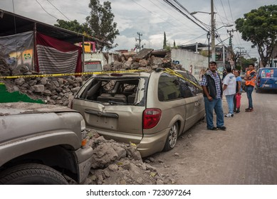 XOCHIMILCO, MEXICO CITY, MEXICO – SEPTEMBER 20, 2017: A building collapsed on vehicles after the earthquake and pedestrians examine the resulting damage.