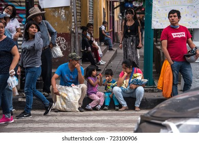 XOCHIMILCO, MEXICO CITY, MEXICO – SEPTEMBER 20, 2017: A family waits on the side of the road as volunteers and pedestrians pass by. Thousands of people were left homeless after the earthquake.