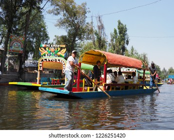 XOCHIMILCO, MEXICO on MARCH 2018: View to several boats with tourists and gondoliers at nice Floating Gardens in mexican city with clear blue sky in warm sunny winter day.