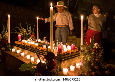 Xoxocotlan, Oaxaca / Mexico - October 30, 2007: Man lighting candles at grave in cemetery decorated for Day of the Dead festival