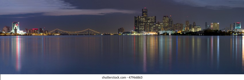 XXL Panoramic of the Detroit Windsor skyline with the Ambassador Bridge connecting the United States with Canada.  Night shot with city lights reflecting in the Detroit River.