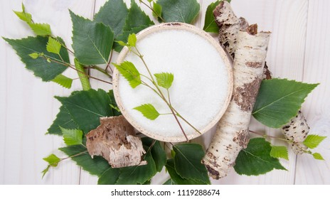 Xylitol - sugar substitute for diabetics. Birch sugar on white wooden background.