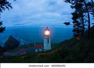 Yachats, Oregon / USA - May 13, 2019: A distant view of Heceta Head Lighthouse, looking toward the ocean, at dusk with an overcast, clouded blue sky - Heceta Head State Park