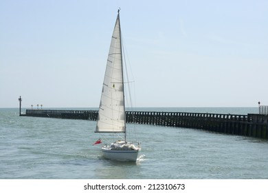 Yacht approaching the harbour at Littlehampton in West Sussex. England. With no visible people.