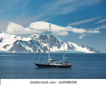 yacht in bay with view to mountains of Antarctica peninsula