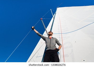 Yacht captain with a beard stands on sail boom on a sailing yacht, holding the rope in his hand and smiling, feeling happy. Adult yachtsman travelling around the world. Copy space