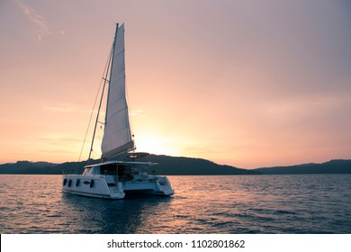 Yacht - Catamaran in the ocean. Sailing at sunset