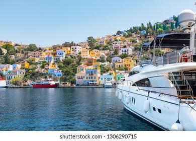 Yacht and colorful neoclassical houses in harbor town of Symi (Symi Island, Greece)