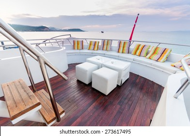 Yacht deck setup with white cube stool furniture preparing for a group party.