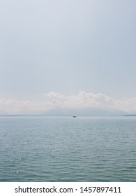 Yacht floating on blue lake Chiemsee against sky and mountains during sunny day