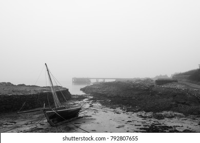 A yacht lying on its side as the tide goes out on a misty beach in Scotland. A jetty can be seen in the misty distance as a freezing mist comes in.