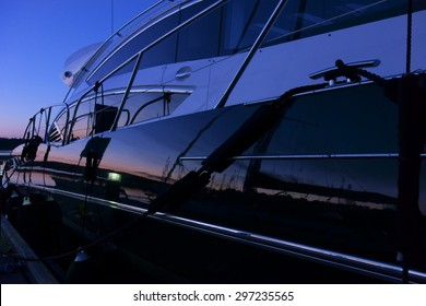 Yacht at the marina captured during a blue hour with setting sun coloring the horizon and reflection of a boat and marina visible from the yacht side