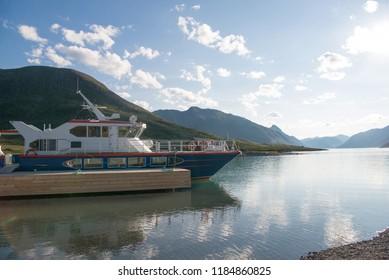 yacht moored in calm water of Gjende lake, Besseggen ridge, Jotunheimen National Park, Norway