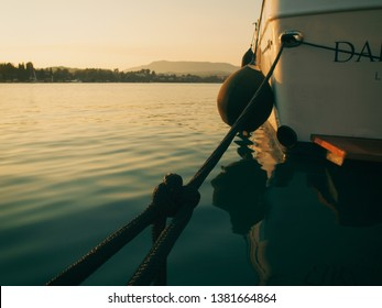 Yacht mooring rope. Moored Boat (luxury yacht) close up in harbor. Ship's side photo shoot from behind. On the side are fenders and mooring ropes. Evening light in marina.