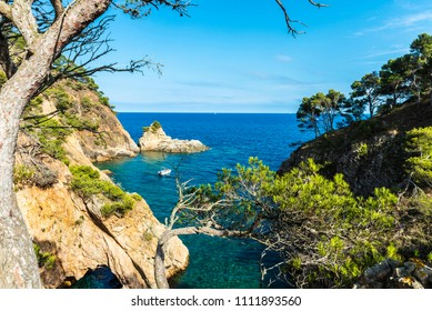 Yacht next to a cliff with a cave in crystal clear waters of the Mediterranean sea in the Costa Brava, Girona, Catalonia, Spain
