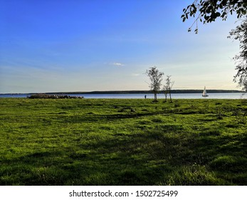 Yacht on the background of a green meadow and a man with trees
