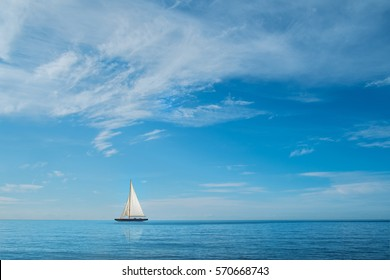 Yacht on horizon at sea with blue sky and clouds