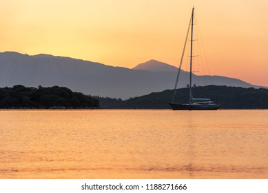 Yacht on sea water surface at sunrise in Greece.