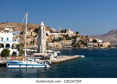 Yacht passing the clock tower of Symi with the skyline of the village in the background