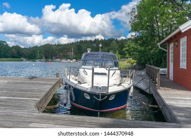 Yacht in port near old wooden pier. Yacht mooring. Mooring rope, bow lines, cleat, pull pit. View of the boat against the blue sea and sky. Horizon. Baltic Sea. Sailing Yachting  Equipment Concept.