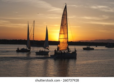 Yacht quietly returned to the place of chartering. The setting sun shines through the sail.