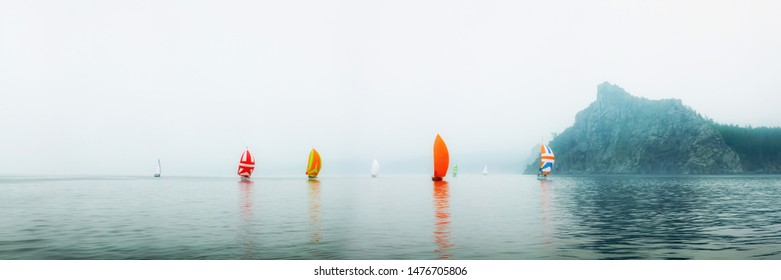 Yacht regatta with an orange sail in a foggy morning floats on the sea
