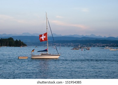 Yacht sailing across Lake Zurich in sunset