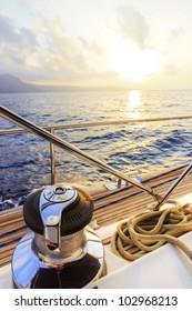 Yacht sailing along the coast at sunset