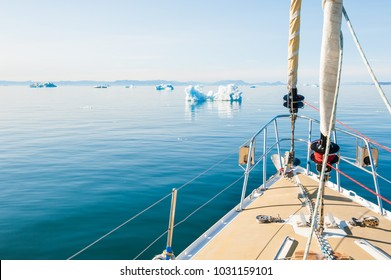 Yacht sailing among icebergs in the Atlantic ocean in Greenland