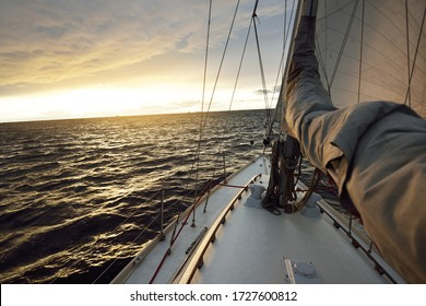 Yacht sailing in an open sea on a winter day at sunset. Close-up view from the deck to the bow, mast and sails. Dramatic sky, golden sunlight through the dark clouds. Epic seascape. North sea, Norway