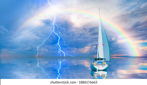 Yacht sailing in open sea at stormy day - Anchored sailing yacht on calm sea with tropical storm and double sided rainbow in the background