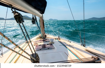 Yacht sailing through the waves of a stormy sea. White deck of a luxury sailing yacht, splashing from waves crashing on the hull. Indian Ocean Holiday Cruise between Islands of Malaysia and Thailand